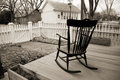 Old rocking chair on wooden porch with white picket fence this black and photo of an sitting a surrounded by a an one Stock Photo