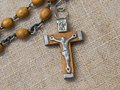 Old rosary with wooden beads detail laid on linen tablecloth Royalty Free Stock Photos