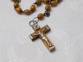 Old rosary with wooden beads detail laid on the white tablecloth Royalty Free Stock Photo