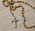 Old rosary with wooden beads laid on linen tablecloth Royalty Free Stock Photos