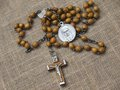 Old rosary with wooden beads laid on linen tablecloth Stock Images