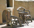 Old roughly carved wooden chairs and table front of stone wall Royalty Free Stock Photography