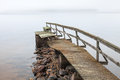 Old ruined wooden pier in foggy morning on the lake Stock Photos