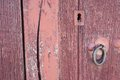 Old run down red painted wooden door and lock closeup of vintage iron Stock Photos
