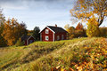 Old rural landscape and autumn colors red cottage surrounded by leaves setting Stock Photography