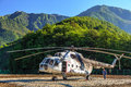 Old Russian helicopter MI-8 stands on landing pad in green Caucasus mountain forest and ready for flight Royalty Free Stock Photo