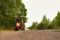 Old Russian tractor on gravel road Royalty Free Stock Photo