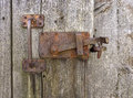Old rusted locking with vertical grasp on the weathered gray wooden wall of a shed Royalty Free Stock Photo