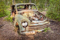 Old rusted scrap car in a forest and weathered Stock Photo