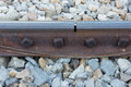 Old rusted screw on railroad rusty metal rail track fixed on st stone Royalty Free Stock Image