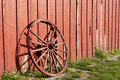 Old rustic wagon wheel beside a red barn. Stock Image