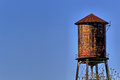 Old, rustic water tower with blue sky background Royalty Free Stock Photo