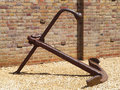 Old rusty boat anchor against a red brick wall on a gravel path Royalty Free Stock Photography