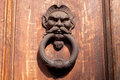 Old rusty door knocker with a human face Stock Photo
