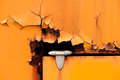 Old rusty hinge detail of orange metal door Royalty Free Stock Photo