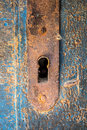 Old rusty keyhole iron plate on beautiful cracked wooden door Royalty Free Stock Photo