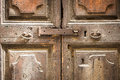 Old rusty latch close up on an ancient wooden door with metal handles. Royalty Free Stock Photo