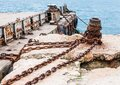 Old, rusty metal mounts and large chains for mooring in the seaport against Royalty Free Stock Photo