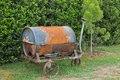 Old and rusty metal wheelbarrow with old barrel on it to decorate the garden Royalty Free Stock Image