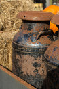 Old rusty milk cans a farm scene with hay pumpkins and Stock Photography