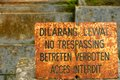 Old and rusty multilingual no treppasing sign english french german indonesian Stock Photos
