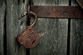 Old rusty opened lock without key. Vintage wooden door, close up concept photo Royalty Free Stock Photo