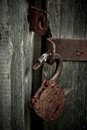 Old rusty opened lock without key. Vintage wooden door, close up concept photo