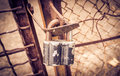 Old rusty padlock fashioned hung on the gates of the fence Royalty Free Stock Photography