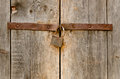 Old rusty padlock on a wooden door metal hanging weathered with rust staining the planks Royalty Free Stock Images