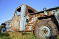 Old rusty pickup full of patina a a junker truck rust and snow tires is parked in the grass Stock Image