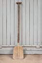 Old rusty shovel against a grey wooden door in a factory Royalty Free Stock Image