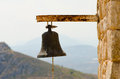 Old rusty steel big bell from church with rope on stone wall in Royalty Free Stock Photo