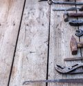 Old, rusty tools lying on a black wooden table. Hammer, chisel, hacksaw, metal wrench.Copy space Royalty Free Stock Photo