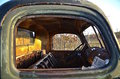 Old rusty truck with broken windows a view through the of a junker reveals only springs left of the seats and much rust Stock Photo