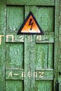 Old rusty warning high voltage sign on cracked wooden surface Royalty Free Stock Photo