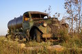 Old rusty water full of patina a junker truck rust and broken window is parked in the grass and brush Stock Images