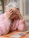 Old sad woman holding pills with at home worried about having to take too many Stock Photo