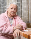 Old sad woman holding pills with at home worried about having to take too many Royalty Free Stock Photography
