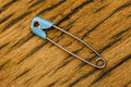 Old safety pin on wood Stock Images