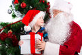 Old santa clause and young little boy holding gift box together sitting looking at each other with christmas tree on background Stock Images