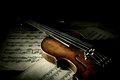 Old scratched violin in shadow music collection on music sheet vintage style Stock Photo