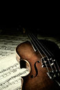 Old scratched violin in shadow music collection on music sheet vintage style Royalty Free Stock Photo