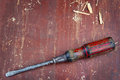 Old screwdriver on red wooden background Royalty Free Stock Photo