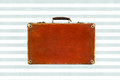 Old shabby brown suitcase with angle bars on watercolor blue stripes background. Royalty Free Stock Photo