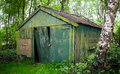 Old shed in the woods an which despite being padlocked is easily enterable Royalty Free Stock Photo