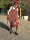 Old sheperd walking on the road ghanerao india march an shepherd wearing a red turban is a during summer transhumance march in Royalty Free Stock Photo