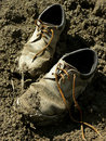 Old shoes muddy worn out in the dirt Stock Image
