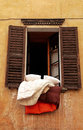 Old shutters window with bedclothes, Italy Royalty Free Stock Photo