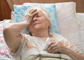 Old sick woman lying at bed Stock Photography