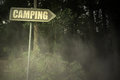 Old signboard with text camping near the sinister forest